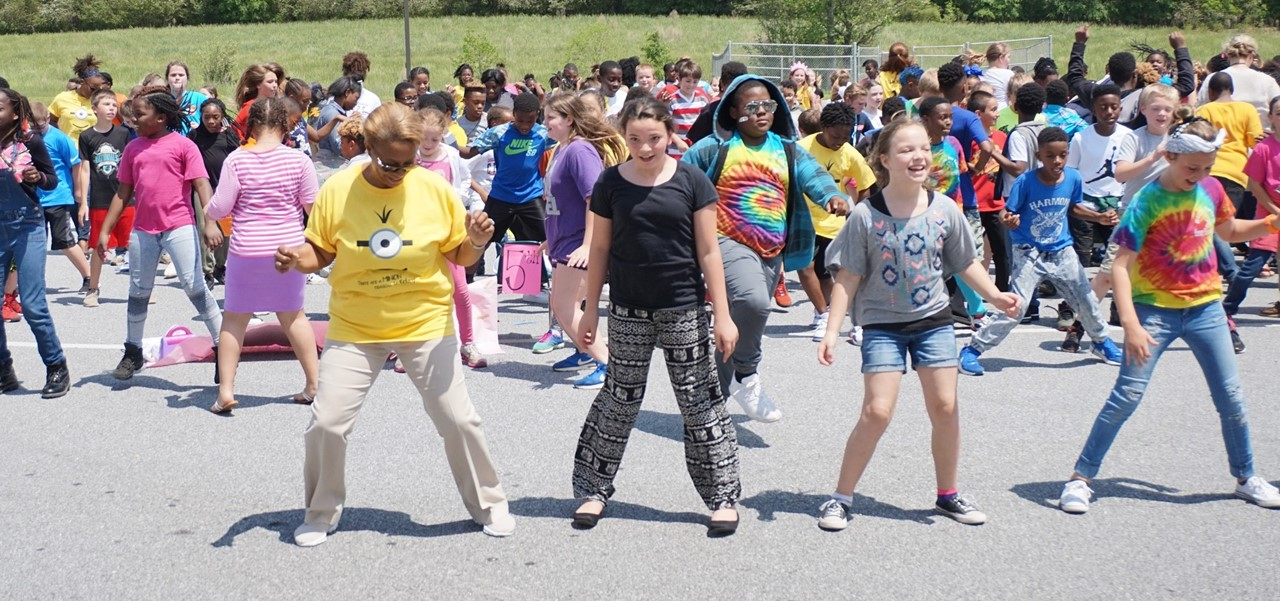 Students dancing in a parking lot