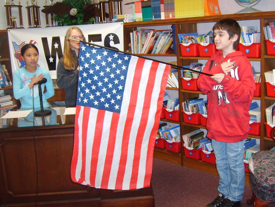 WLES students saying the Pledge of Allegiance while holding the American Flag.
