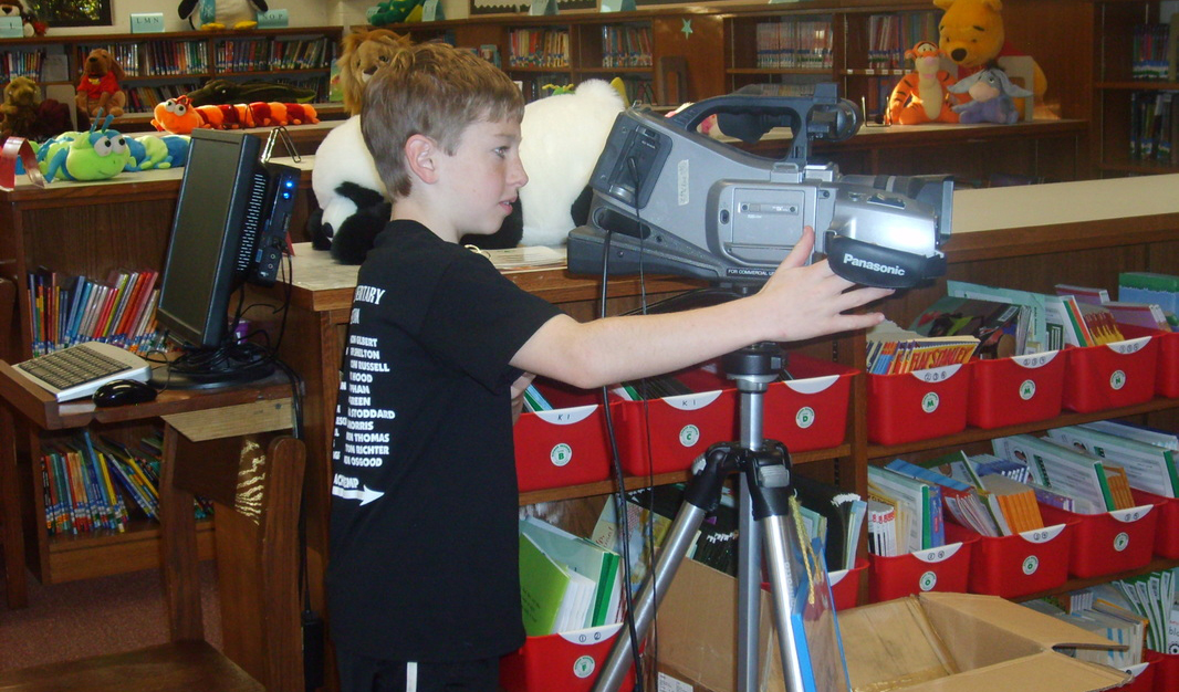 WLES student using a camera to film the morning show.