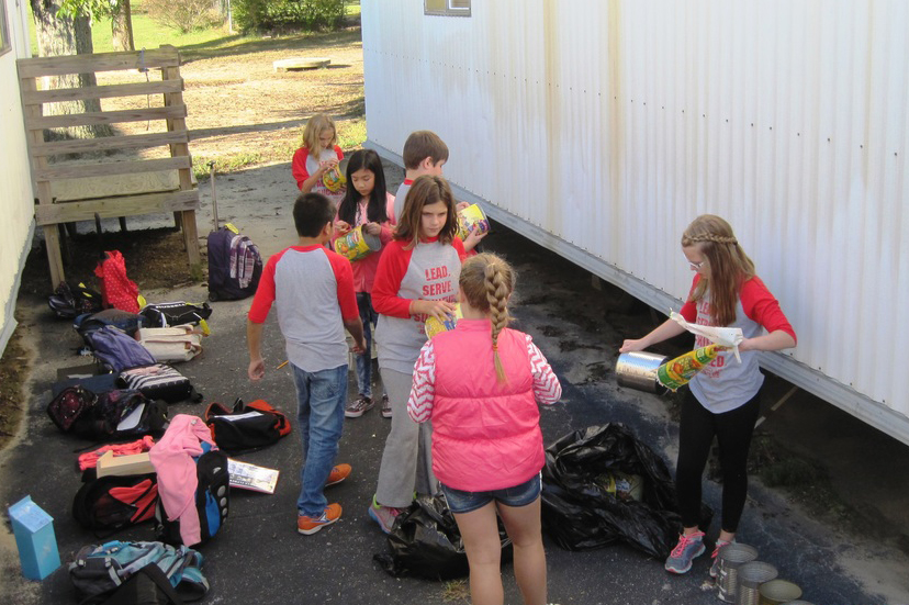 Focus students working outside to recycle cans.