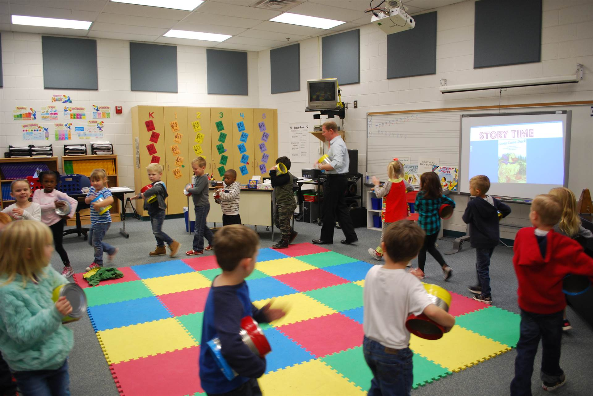 Students walking in a circle playing drums in art class.