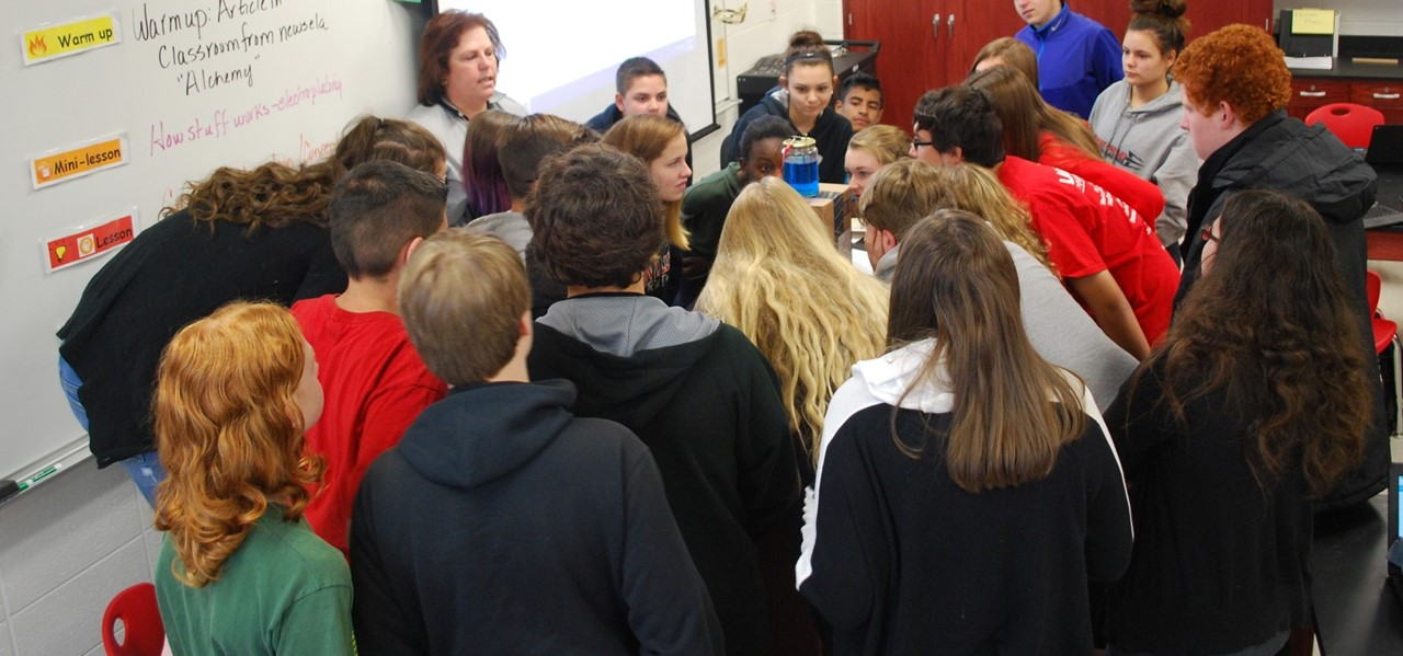 LMS students watch a science experiment at the front of their classroom.