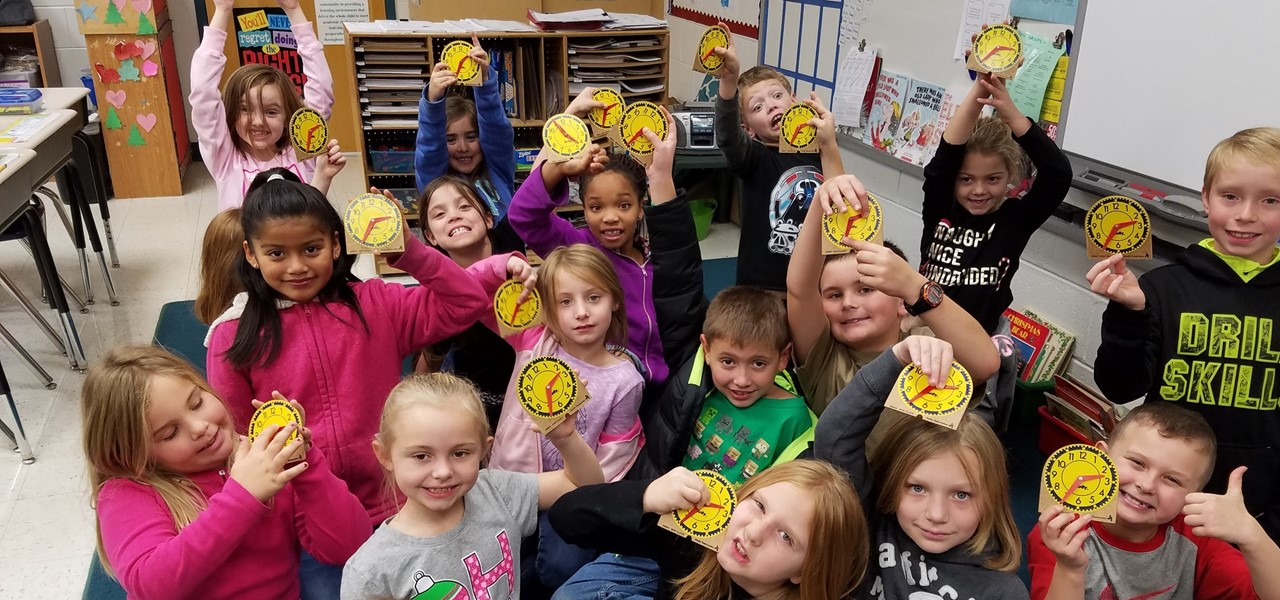 Students holding clocks while learning about telling time.