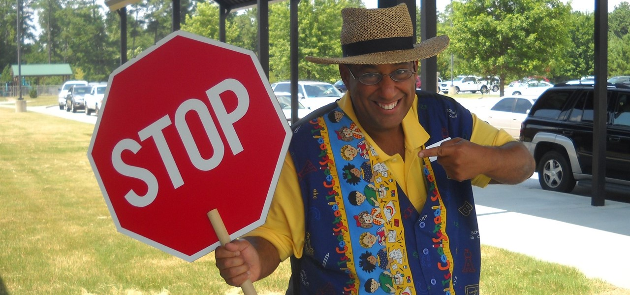 Teacher holding a stop sign in the bus lane.