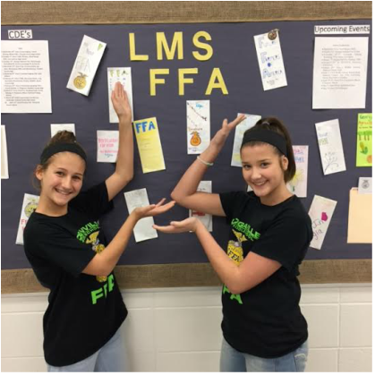 Students standing next to an FFA bulletin board.