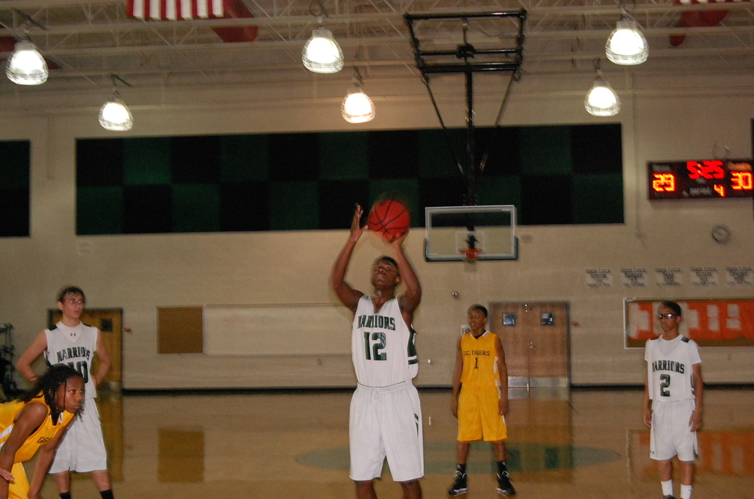 YMS boy shooting a basketball during a game.
