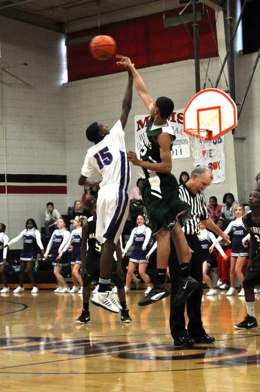 Boy blocking a basketball shot.