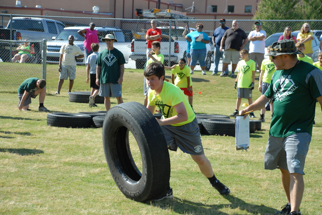 Student flipping a tire at football camp.