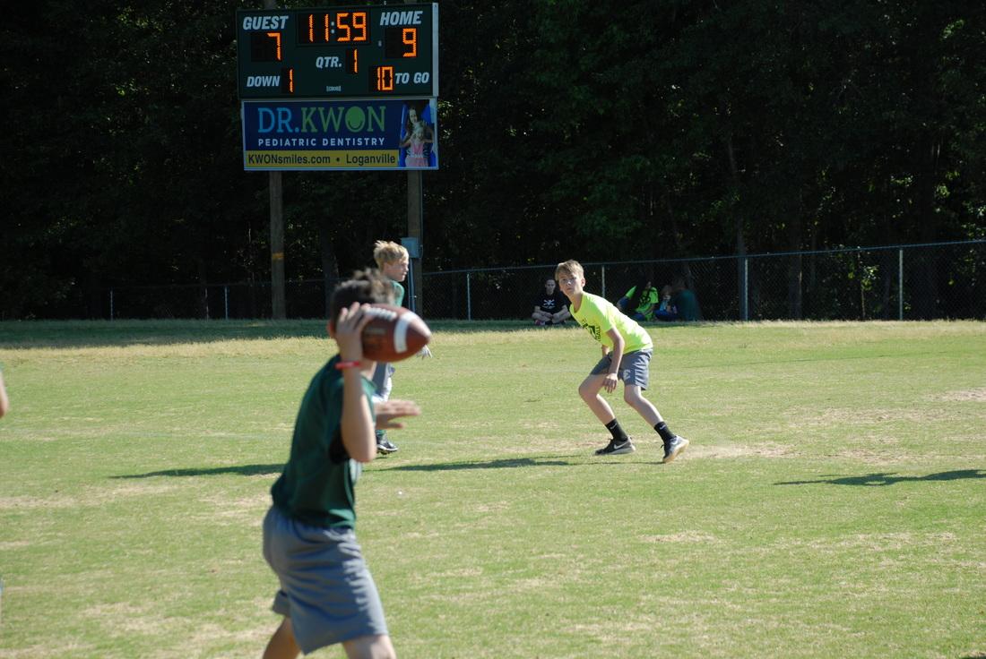 Student passing a football at football camp.