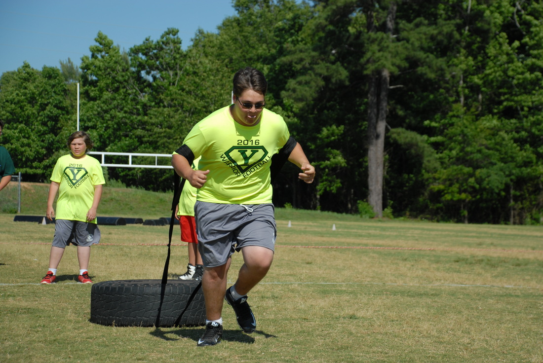 Student pulling a tire at football camp.