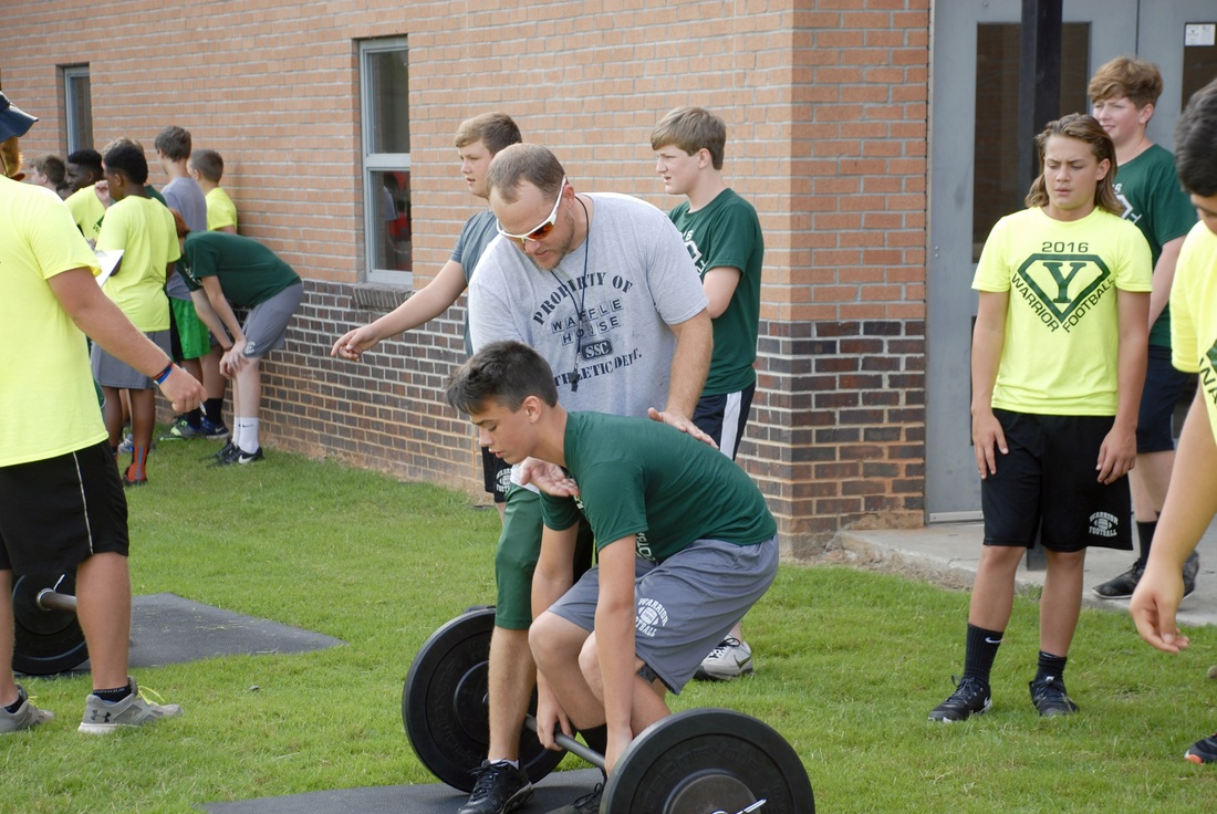 Student lifting weights at football camp.