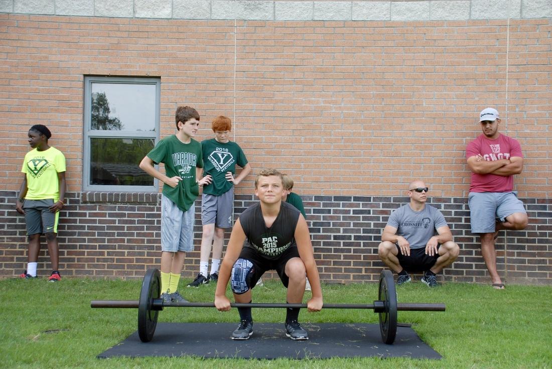 Student lifting weights at football camp.