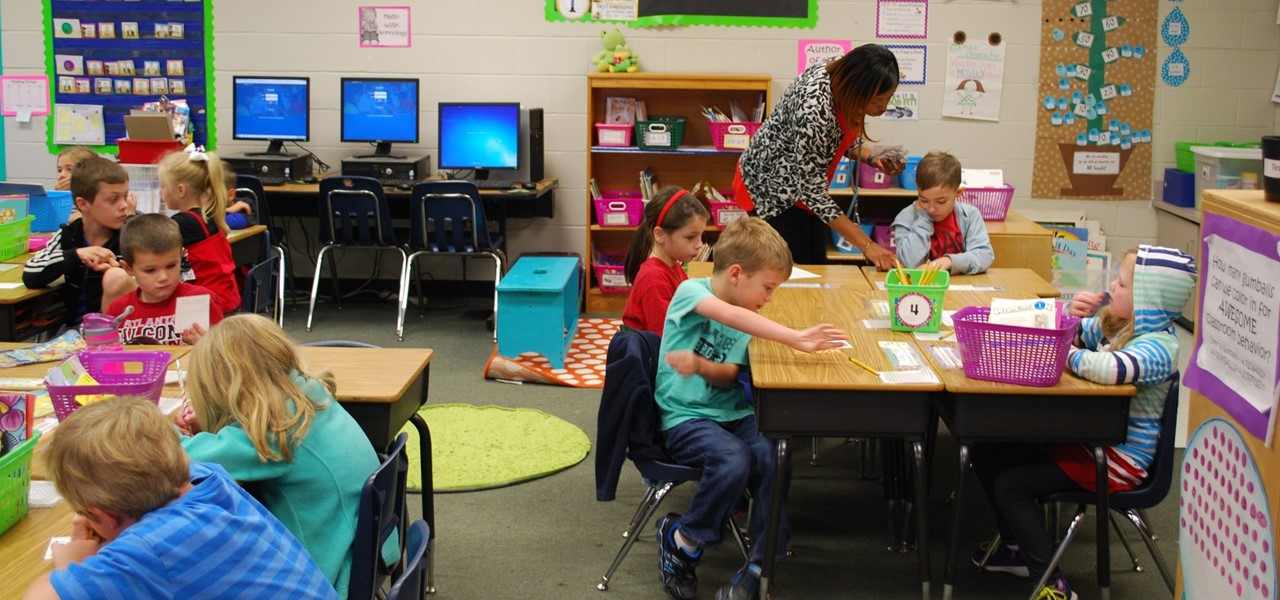 Teacher helping a student at their desk.