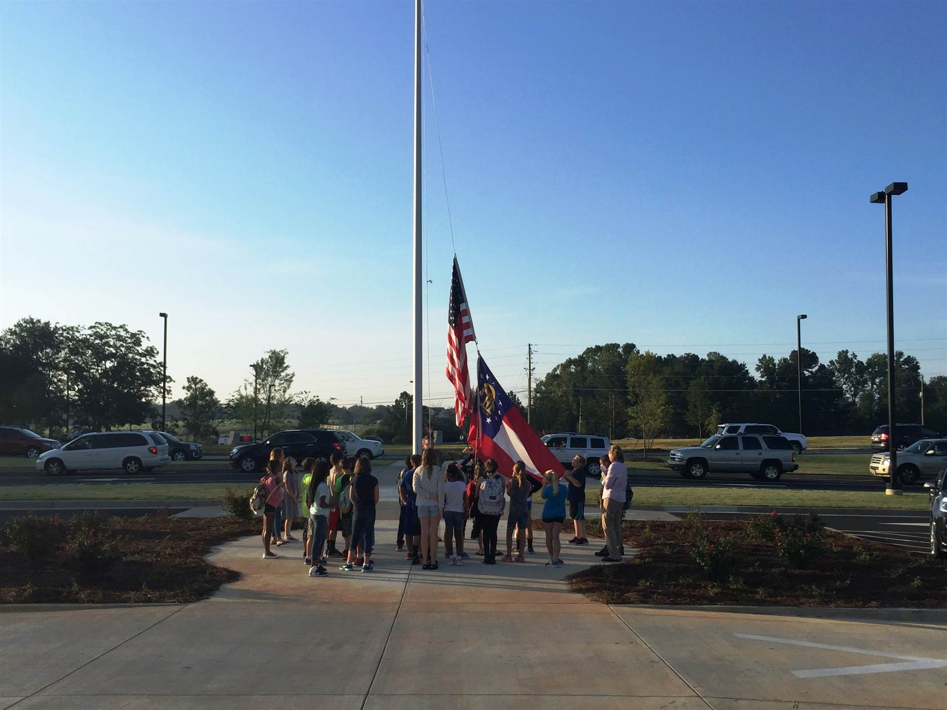 Safety Patrol students raising the flag up outside the school.