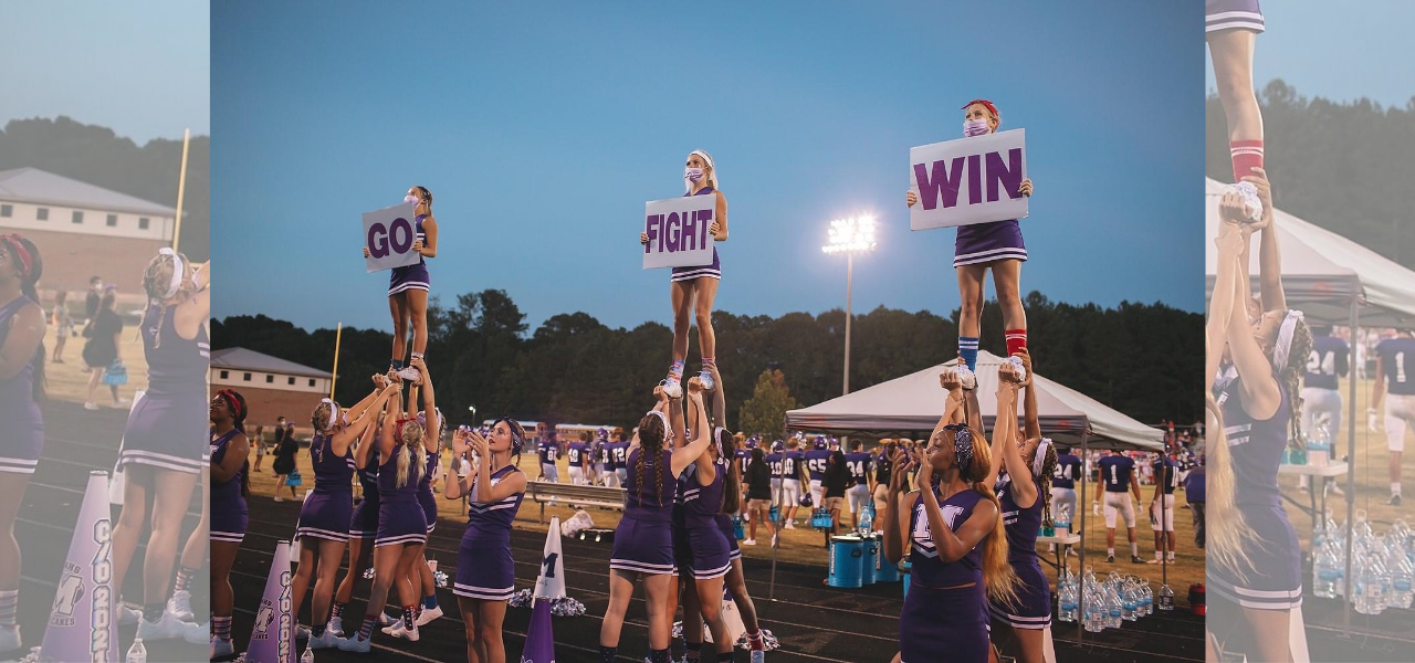 MAHS Cheerleaders in purple uniforms doing a stunt. Three groups of cheerleaders each hold one girl in the air. They hold signs that read Go Fight Win.