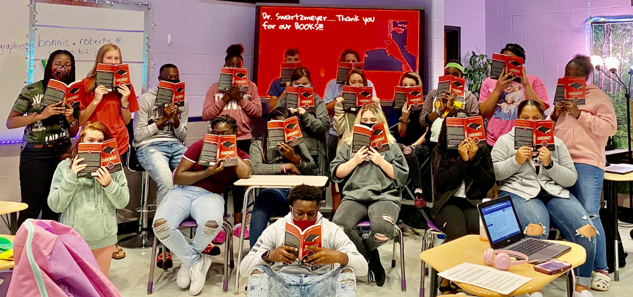 "A group of students wearing masks hold up copies of Fahrenheit 451. A screen in the background with white text on a red background reads, ""Dr. Swartzmeyer... thank you for our books."""