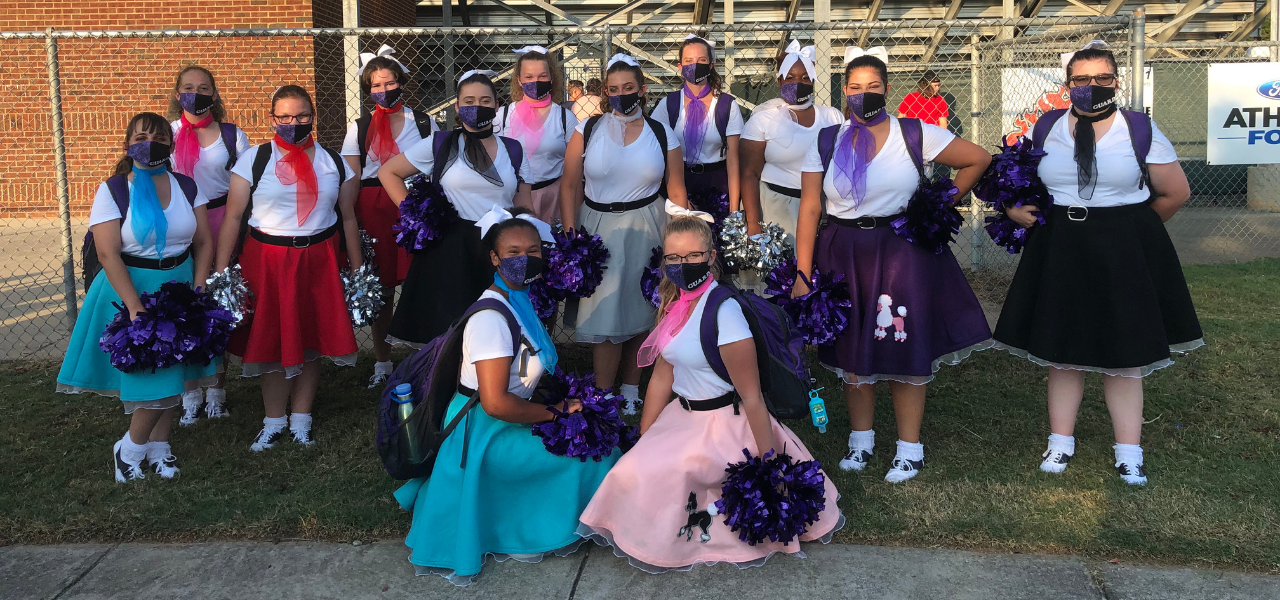 Group of colorguard members wearing white shirts and poodle skirts in various colors. All are wearing masks.