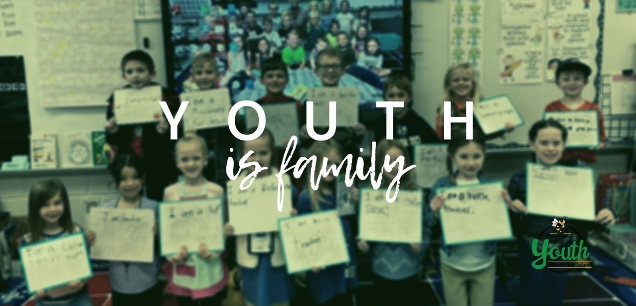 Youth is Family picture of students holding papers